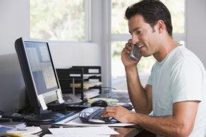 Homme au téléphone devant un ordinateur